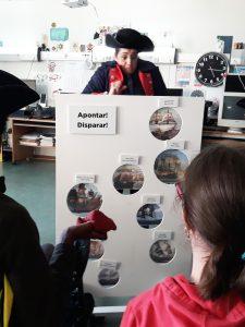 Os alunos atiram uns sacos cheios de areia para um painel onde se encontram navios de piratas.