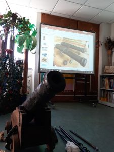 Colocado no chão da sala, encontra-se uma réplica de um canhão e no quadro interativo está uma fotografia de vários tipos de canhões.