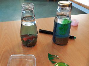 Dois aquários feitos pelos alunos: frascos em vidro cheios de líquido verde e azul, com areia no fundo e bonecos que representam peixes a nadar.