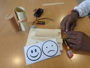 Aluno com um smile e um unsmile e materiais eléctricos para o projecto