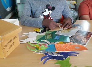 Uma aluna faz colagens em cartões para construir o seu peixe bizarro.