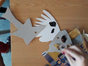 Uma aluna cola pedaços de papel sobre três cartolinas que se encontram unidas com ataches e formam o seu peixe bizarro.