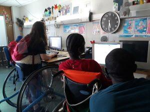 Os alunos encontram-se a trabalhar diante do seu computador e o Va observa e dá instruções.