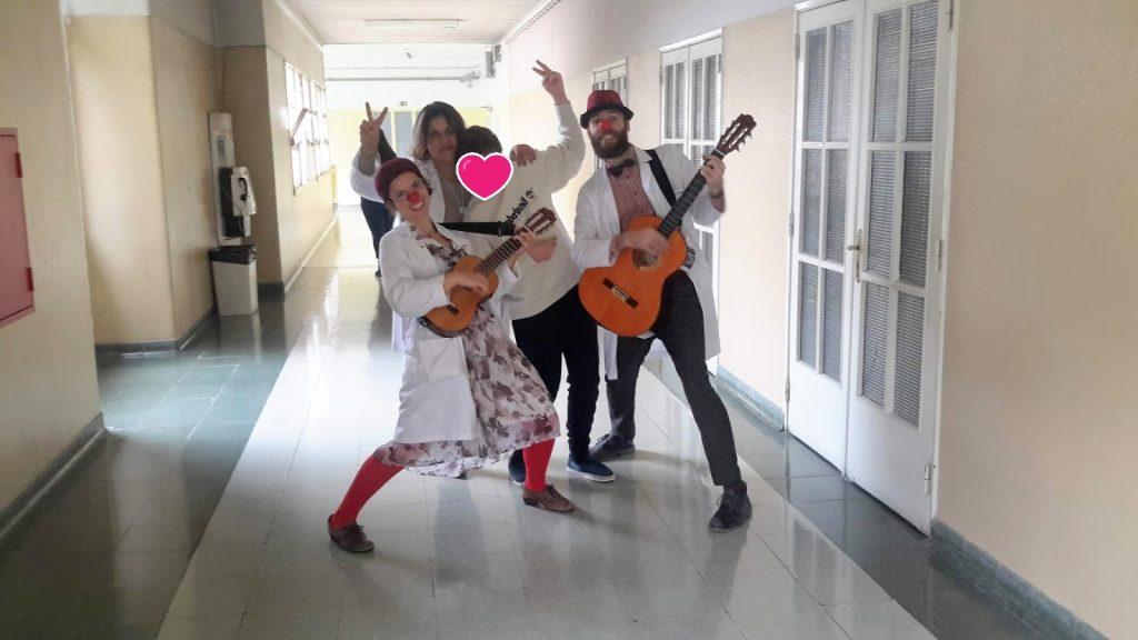 Doutores palhaços com guitarras, aluno e professora no corredor do hospital