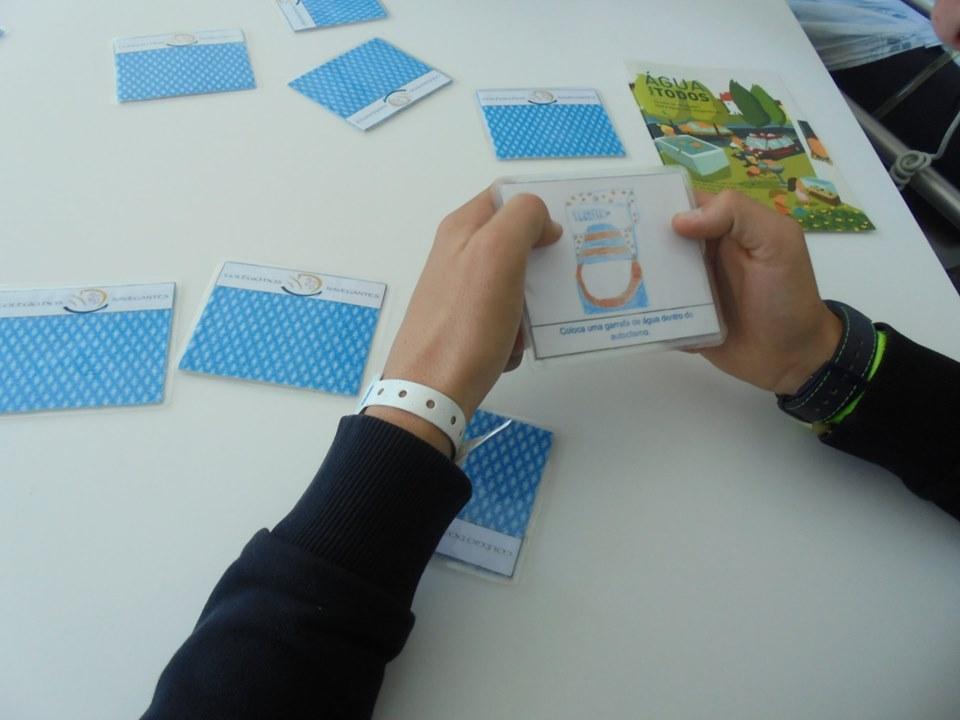 Alunos com cartão de um jogo de memória e cartões sobre a mesa