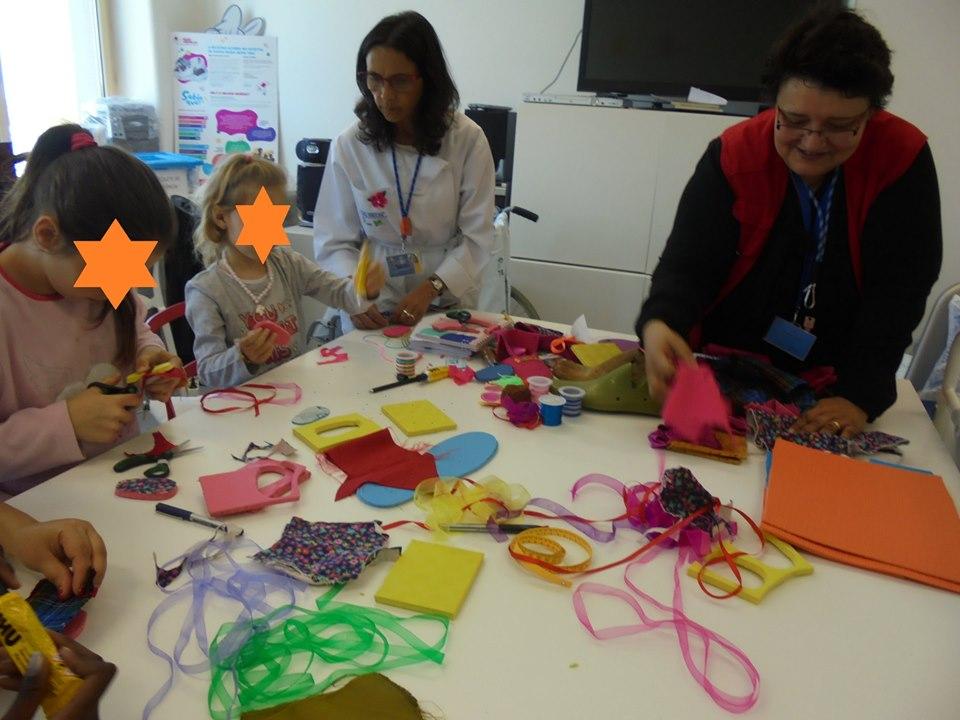 Professora, alunos, Evelina e mesa com materiais de trabalhos manuais