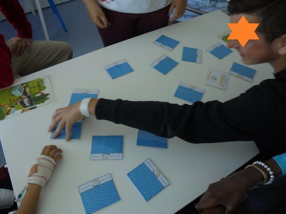 Alunos com cartões de um jogo de memória sobre a mesa