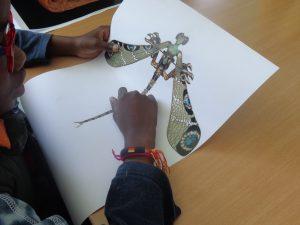 Mãos de aluno com animal imaginário impresso