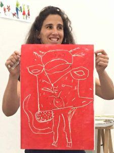A mediadora cultural, Joana, mostra o produto final do trabalho realizado pelos alunos: uma gravura que representa um animal imaginário em vermelho.