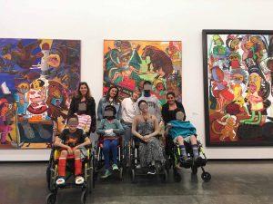 Uma fotografia do grupo em frente a três quadros de grandes dimensões de Paula Rego.