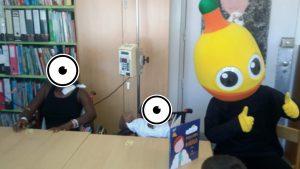 Mascote do Pirilampo Mágico com aluno e livro