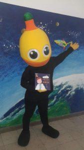 Mascote do Pirilampo Mágico com aluno com livro