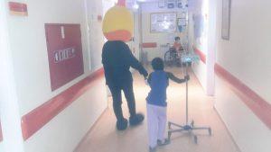 Mascote do Pirilampo Mágico com aluno no corredor