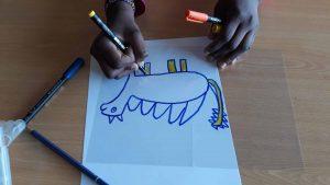 Uma aluna desenha o seu animal imaginário, semelhante a um dinossauro, sobre uma folha de acetato.