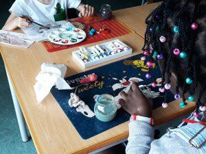 Dois alunos pintam com tinta acrílica pedaços de fimo para a construção de beatas de cigarro.
