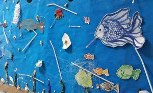 A exposição final no jornal de parede: um painel azul (mar) com peixes feitos em papel envolvidos em plástico e outros lixos.