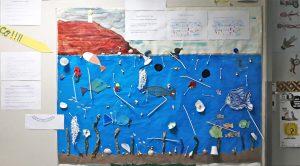 Visão geral da exposição: um mar com fauna e flora rodeada de palhinhas, redes, cotonetes, copos e pratos descartávis de plástico assim como textos informativos sobre o assunto.