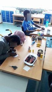 Três alunos a construirem o seu livro miniatura.