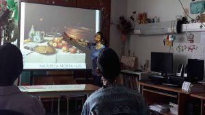A Mariana faz o estudo de uma natureza morta projetada no quadro interativo e os alunos observam e participam na conversa.