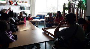 Visão geral da sala da escola com alunos e duas mediadoras culturais a conversarem.