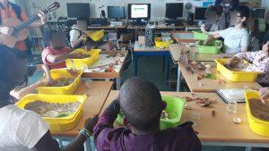 """A sala da escola com as mesas dispostas em U. Cada aluno tem o seu tabuleiro com areia da praia, água, conchas que vai moldando até construir a sua paisagem. Um dos voluntários do projeto """"Música nos hospitais"""" toca guitarra."""