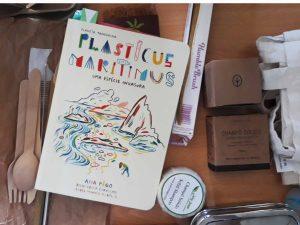 Numa mesa pode ver-se o livro Plasticus maritimus e alguns objetos e produtos substituos do plástico: talheres, palhinhas e escova de dentes em bambu, champô sólido e sacos em pano.
