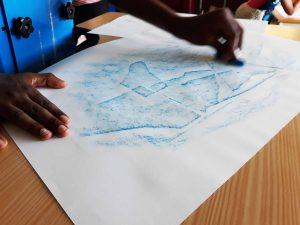 Um aluno passa com lápis de cera azul sobre os pedaços de papel que colou e surgem traços e contornos mais escuros e claros.