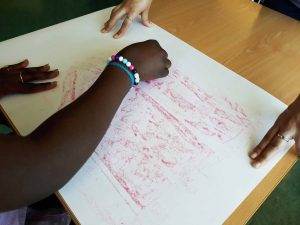 Uma aluna passa com lápis de cera cor-de-rosa sobre os relevos deixados pelos papeis que rasgou e colou e surgem formas de uma casa e de um jarro com flores.