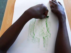 Um aluno passa numa folha branca que se encontra por cima dos relevos deixados pelos pedaços de papel lápis de cera verde.