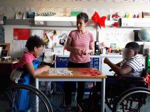 A Tânia trabalha com dois alunos mais novos que partilham a mesma secretária e rasgam pequenos pedaços d epapel enquanto conversam sobre o trabalho que vão fazer.