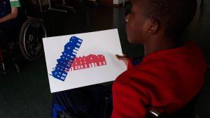 Um aluno mostra a su serigrafia feita: a fachada do Centro Cultural de Cascais a vermelho e a azul sobrepostas.