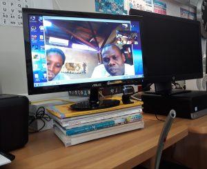 No monitor do computador encontram-se em grande plano os dois técnicos do Parque da Gorongosa em videoconferência com Alcoitão.