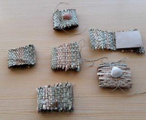 Alguns livros, cinco, feitos com o tecido de fibras vegetais como capa, com folhas de papel presas com cordel e enfeitados com conchas.
