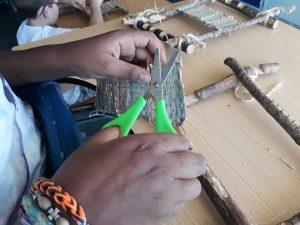 Um aluno apara com uma tesoura algumas pontas soltas do seu tecido já retirado do tear.