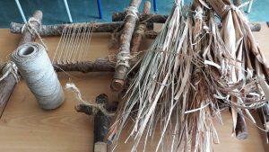 Uma mesa com folhas secas, cordel e teares pequenos feitos com troncos de árvores.