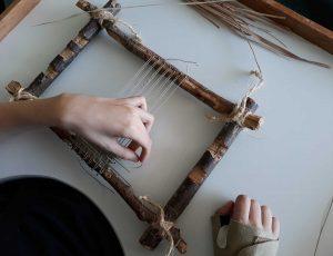 Um aluno a tecer no seu tear apenas com uma mão.