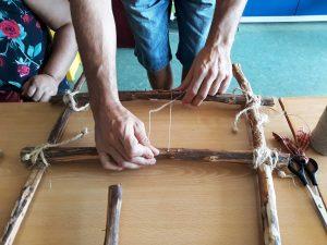 O Luís prepara um tear com cordel que prende em pequenos pregos que se encontram nos troncos.