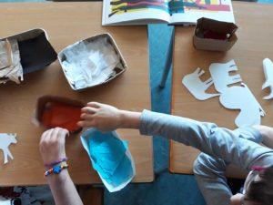 Os alunos escolhem os papeis de seda para reproduzir a técnica utilizada nas ilustrações da obra.