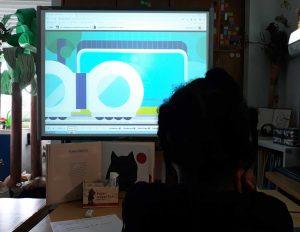 os alunos observam uma aula na plataforma projetada no quadro interativo.