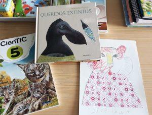 Em cima da secretária, está um manual didático de Ciências Naturais, a obra de Arianna Papini e um trabalho de desenho e colagem elaborado por uma aluna.