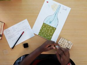 """Um aluno acaba o seu trabalho de desenho e colagem e utiliza carimbos com as letras do alfabeto para escrever a palavra """"extinto""""."""