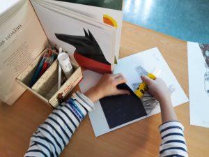 Um aluno, diante da página aberta onde se encontra o animal por ele escolhido, elabora o seu trabalho de desenho e colagem.