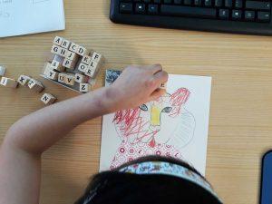 """Uma aluna termina o seu trabalho de desenho e colagem, imprimindo a palavra """"extinto"""" com carimbos."""