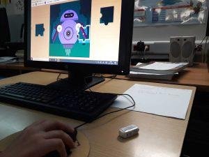 Uma aluna trabalha individualmente na plataforma ubbu e constrói o puzzle de um robô.