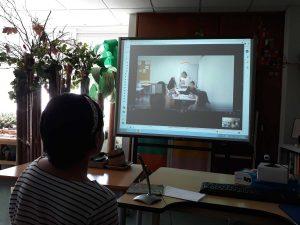 A aluna assiste à apresentação e descrição de um espaço da escola através de videoconferência com o auxílio de um quadro interativo.