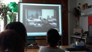 A aluna e encarregada de educação assistem através de videoconferência a uma aula de apresentação dos colegas da turma.