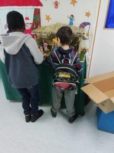 Dois alunos observam o presépio