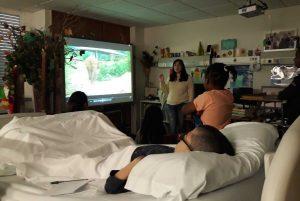A Dra. Sandra fala para um grupo de alunos sobre o que se pode visionar no quadro interativo (elefantes).