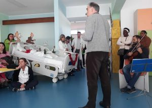 O maestro Lalov fala para um público variado. Podemos ver alunos, pacientes, fisioterapeutas, médicos, mães entre outros.