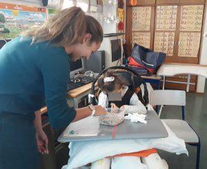 A nutricionisra Andreia oferece a uma aluna leguminosas para que ela possa sentir a textura.